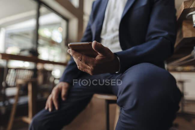 Крупный план бизнесмена, держащего мобильный телефон в кафе — стоковое фото