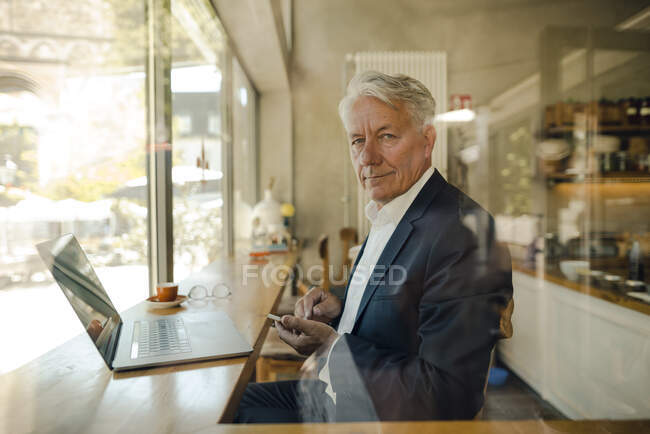Portrait of senior businessman with cell phone and laptop in a cafe — Stock Photo
