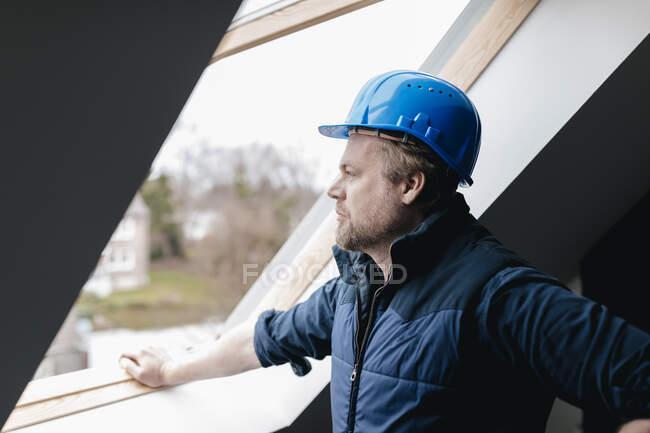 Архітектор дивиться у вікно на будівельному майданчику — стокове фото