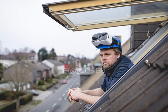 Arquitecto con gafas VR en su casco de seguridad, mirando desde el techo - foto de stock