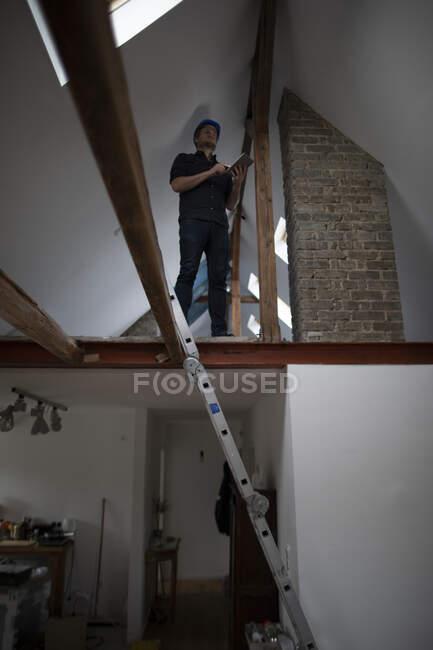 Arquitecto trabajando en la construcción sentarse de una conversión loft - foto de stock
