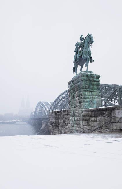 Kaiser Wilhelm I estatua por Hohenzollern Puente sobre el río Rin en la ciudad contra el cielo durante el invierno - foto de stock
