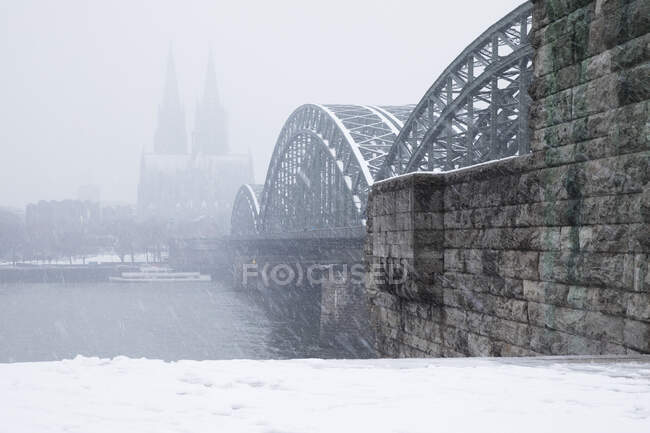 Puente de Hohenzollern sobre el río Rin por la catedral de Colonia durante las nevadas en la ciudad contra el cielo - foto de stock
