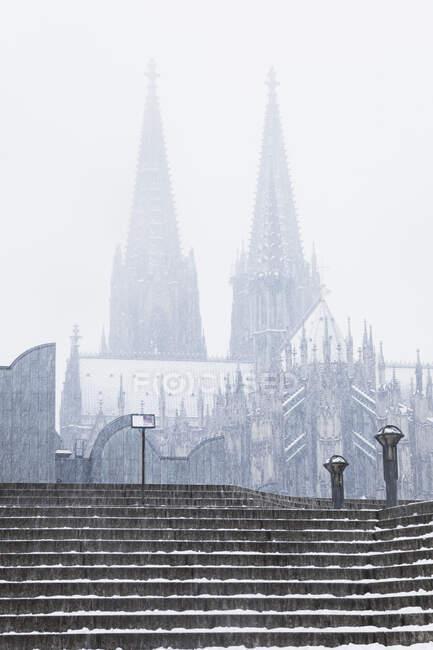 Vista en ángulo bajo de la Catedral de Colonia y el Museo Ludwig durante las nevadas en la ciudad contra el cielo - foto de stock