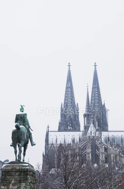 Vista de ángulo bajo de la estatua del Káiser Guillermo II contra la catedral de Colonia durante el invierno en la ciudad - foto de stock