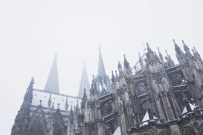 Vista de ángulo bajo de la catedral de Colonia durante las nevadas contra el cielo - foto de stock