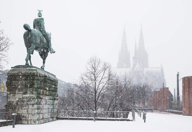 Estatua del Káiser Guillermo II contra la catedral de Colonia durante el invierno en la ciudad - foto de stock