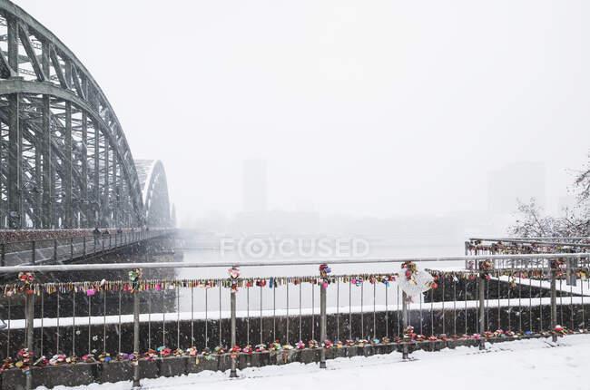 Candados en barandilla por Hohenzollern Puente sobre el río Rin contra el cielo durante las nevadas - foto de stock