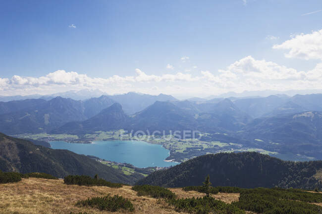 Scenic view of Wolfgangsee and Dachstein Mountains against blue sky — Stock Photo