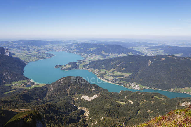Idyllic shot of lake and mountains against blue sky — Stock Photo