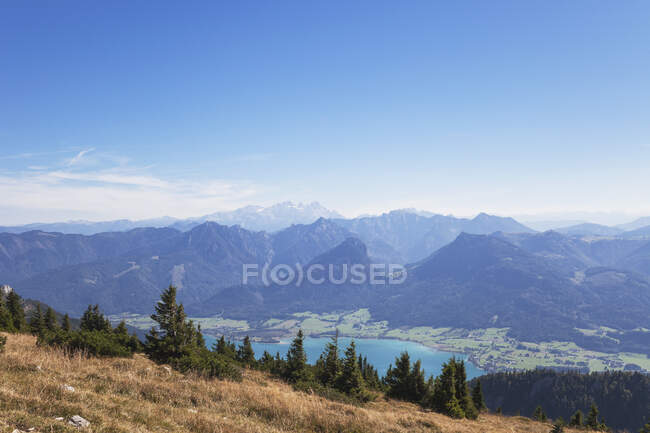 Idyllic shot of mountains and Lake Wolfgangsee against blue sky — Stock Photo