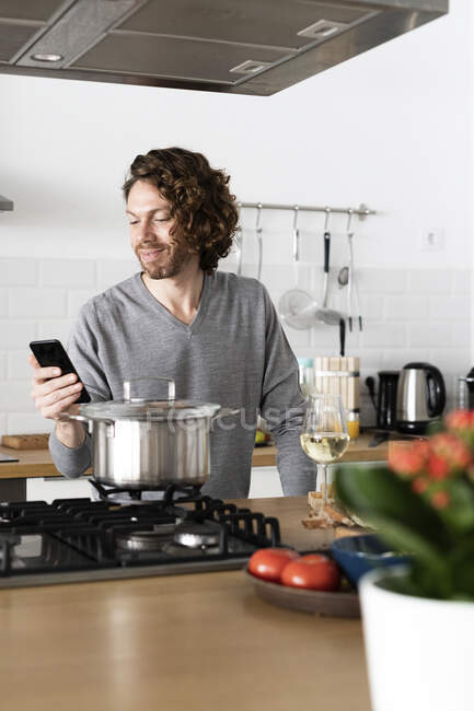 Smiling man using cell phone in kitchen at home — Stock Photo