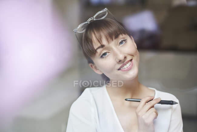 Portrait of smiling young businesswoman with  glasses and pencil behind glass pane — Stock Photo