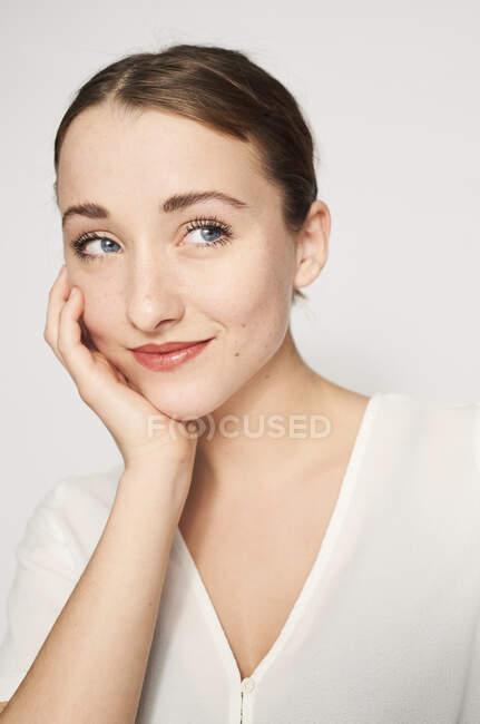 Retrato de una joven sonriente con la cabeza en la mano - foto de stock