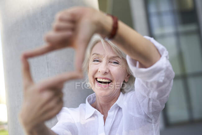 Portrait of laughing mature woman shaping frame with her fingers — Stock Photo