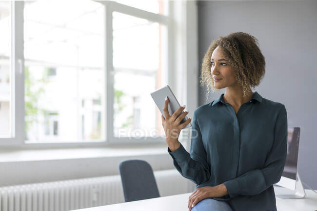 Smiling oung businesswoman with digital tablet in office — Stock Photo