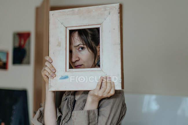 Портрет художниці зі студії, який дивиться крізь картинну раму. — стокове фото