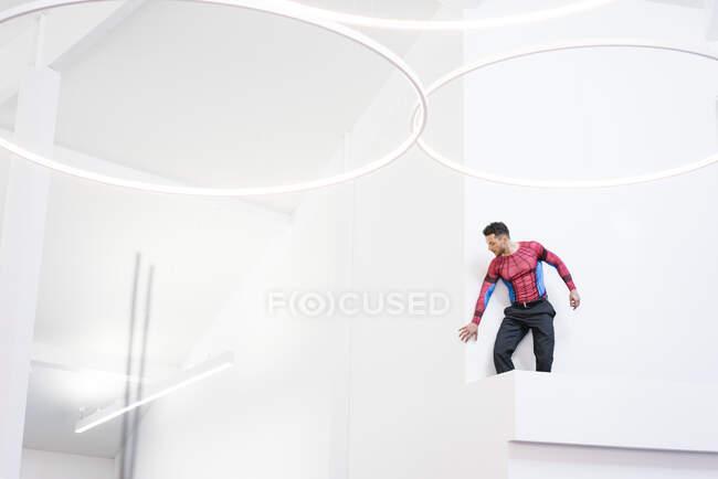 Empresario disfrazado de superhéroe en la oficina - foto de stock