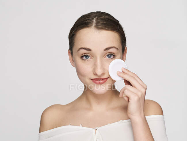 Portrait of smiling young woman with cotton pad — Stock Photo