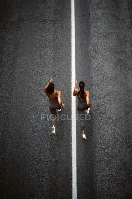 Vista superior de dos hermanas gemelas deportivas corriendo en una calle - foto de stock