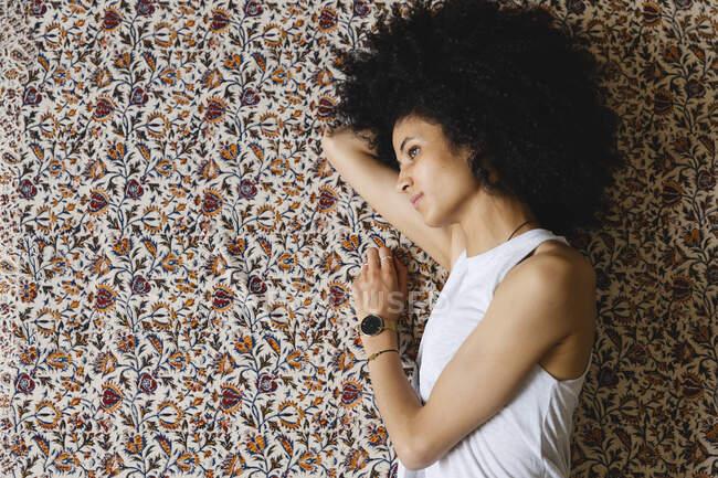 Mujer joven acostada de costado en la alfombra - foto de stock