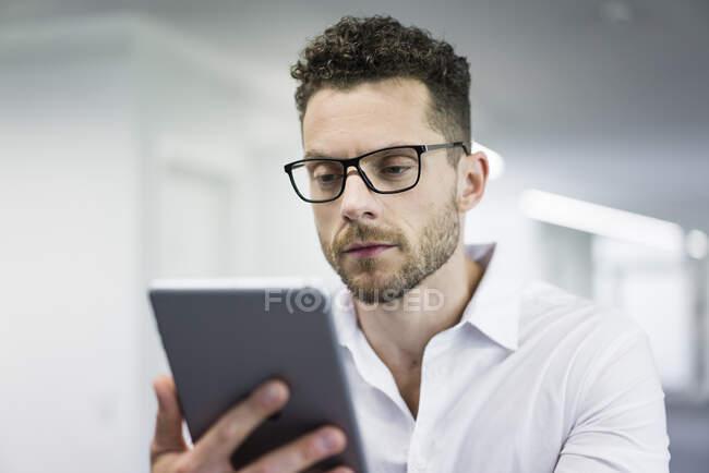 Geschäftsmann schaut im Büro auf Tablet — Stockfoto