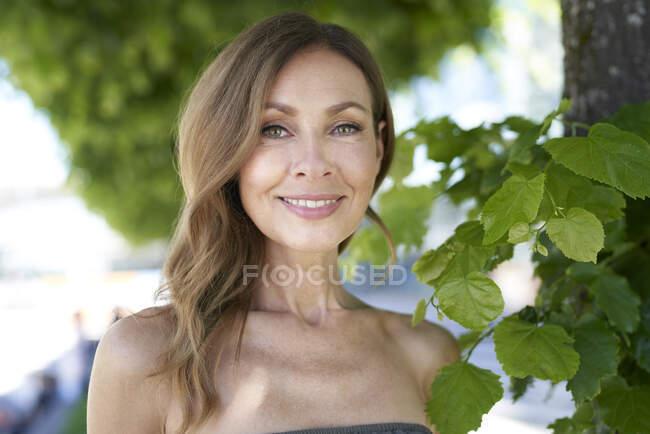 Retrato de mujer madura, árbol en el fondo - foto de stock