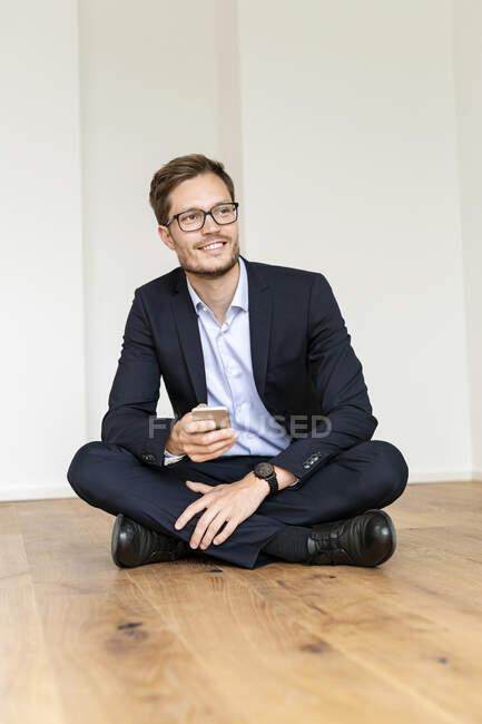 Усміхнений бізнесмен сидить на підлозі з мобільним телефоном. — стокове фото