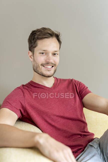 Ritratto di un uomo sorridente seduto su un divano — Foto stock