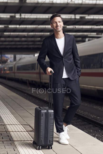 Зрілий чоловік з вагонеткою на станції. — стокове фото