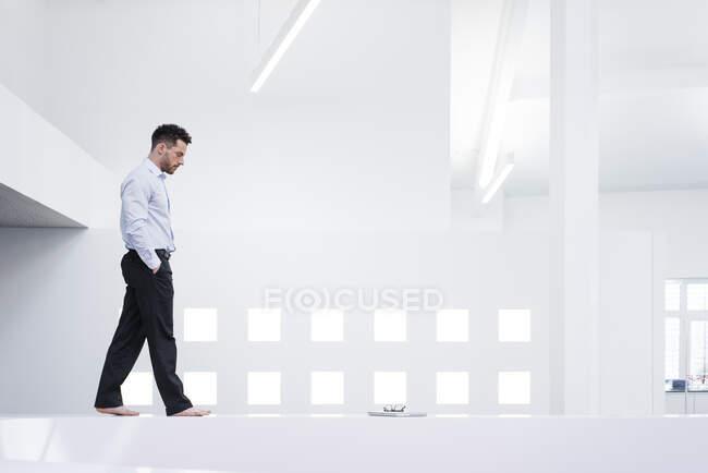 Босоногий бізнесмен ходить по приймальні в офісі. — стокове фото