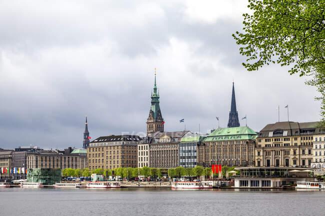Vista de la ciudad con el ayuntamiento y St Nikolai Memorial y Alster Interior en primer plano, Hamburgo, Alemania - foto de stock
