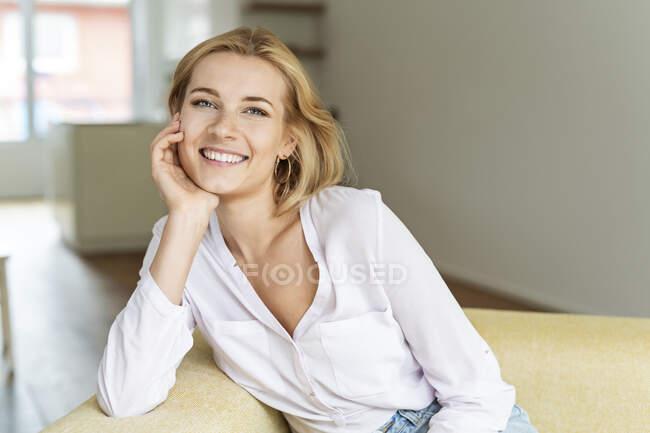 Retrato de una joven feliz sentada en un sofá - foto de stock