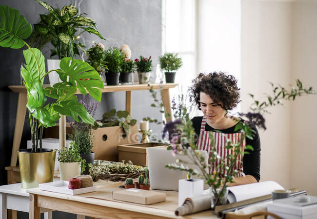 Young woman using laptop in a small shop with plants — Stock Photo