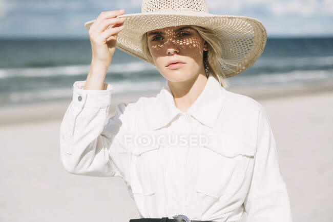 Portrait of blond young woman wearing white shirt and summer hat on the beach — Stock Photo