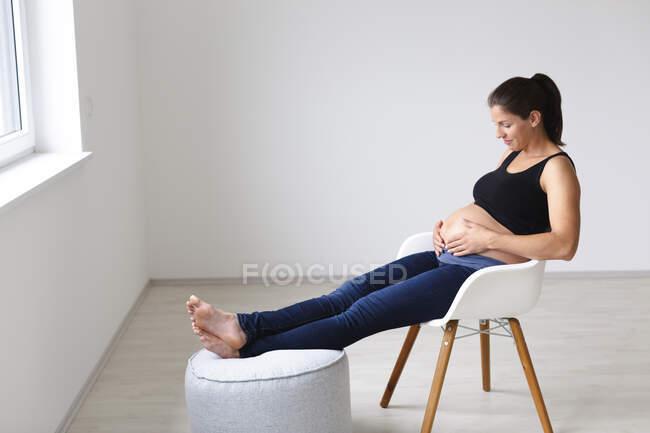 Молодая беременная женщина сидит на стуле и думает о будущем — стоковое фото