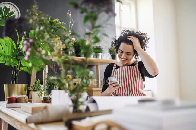 Щаслива молода жінка користується мобільним телефоном у маленькому магазині з рослинами. — стокове фото