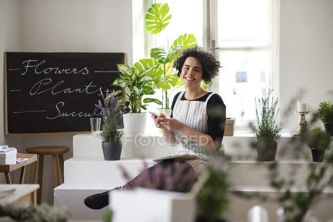 Portrait of smiling young woman using cell phone in a small shop with plants — Stock Photo