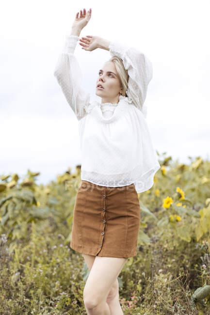 Retrato de una joven rubia con blusa blanca bailando en el campo de girasol - foto de stock