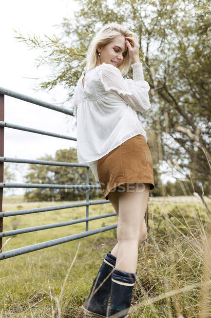 Retrato de una joven rubia con blusa blanca, mini falda y botas Wellington - foto de stock