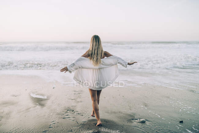 Young blond woman wearing bikini and white dress at the beach in the morning — Stock Photo