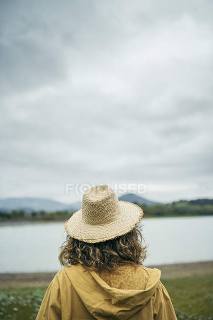Rear view of young woman wearing straw hat, looking to a lake — Stock Photo