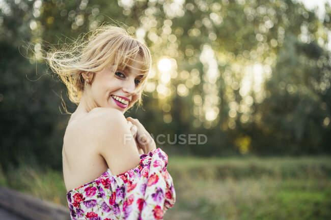 Портрет счастливой молодой женщины в летнем платье с цветочным дизайном на природе — стоковое фото