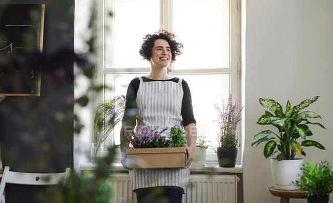 Щаслива молода жінка тримає квіти в картонній коробці в маленькому магазині. — стокове фото