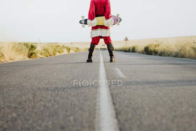 Sección baja de Santa Claus sosteniendo un longboard en la carretera del país - foto de stock