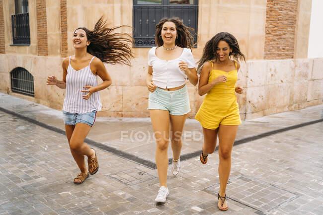 Tre amiche felici che corrono in città — Foto stock