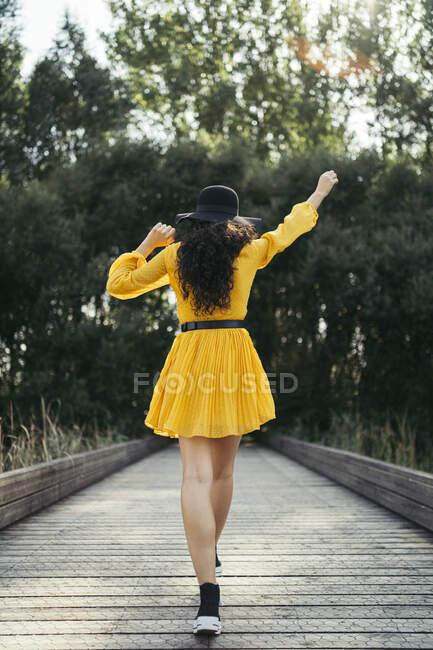 На задньому плані - молода жінка в чорному капелюсі і жовтому платті, яка насолоджується ходьбою по дерев