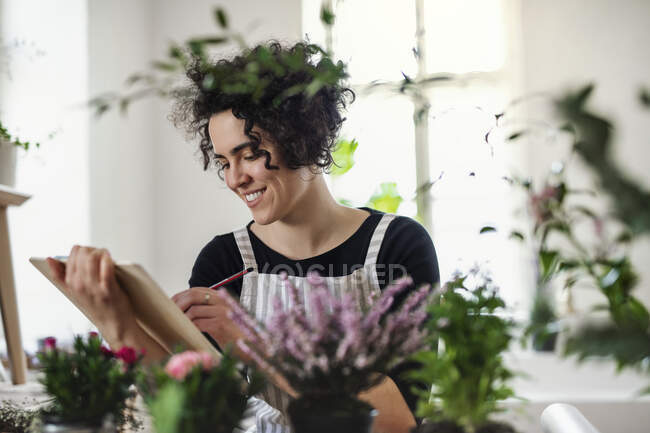 Smiling young woman with clipboard in a small shop with plants — Stock Photo