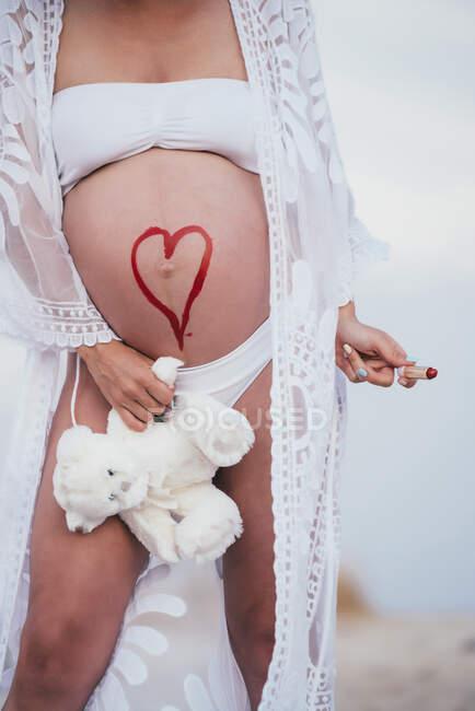 Беременная женщина с нарисованным сердцем на животе держит плюшевого медведя — стоковое фото