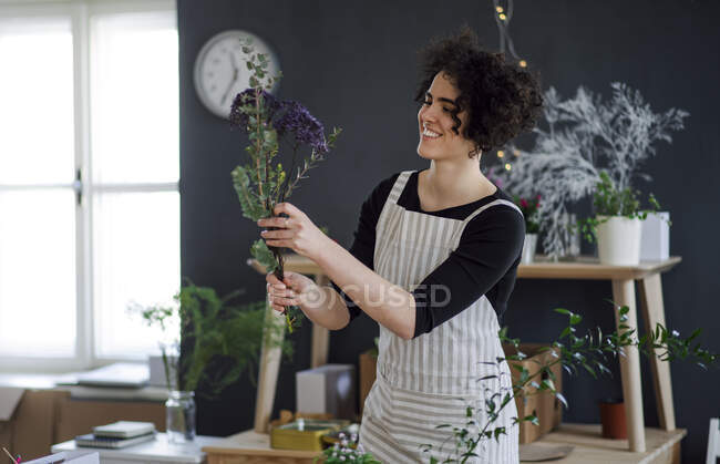 Smiling young woman arranging flowers in a small shop — Stock Photo